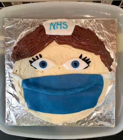 Cake decorated to look like a face with a Covid mask on