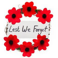 Image of a poppy wreath with Lest We Forget written across