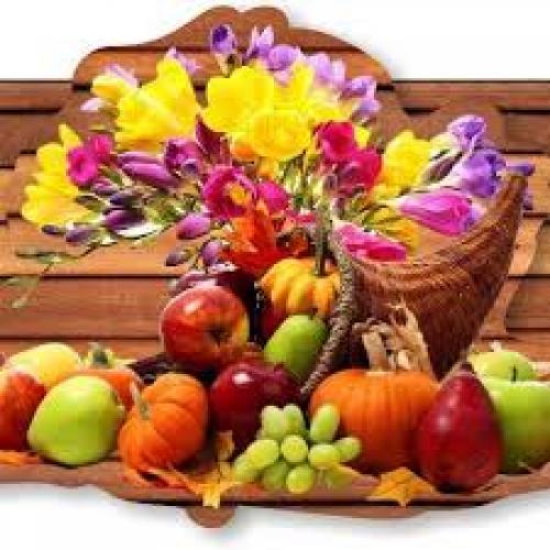 An arrangement of fruit and flowers in a wicker basket