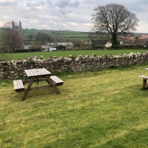 Photo of picnic benches in situ overlooking a view of surrounding area.